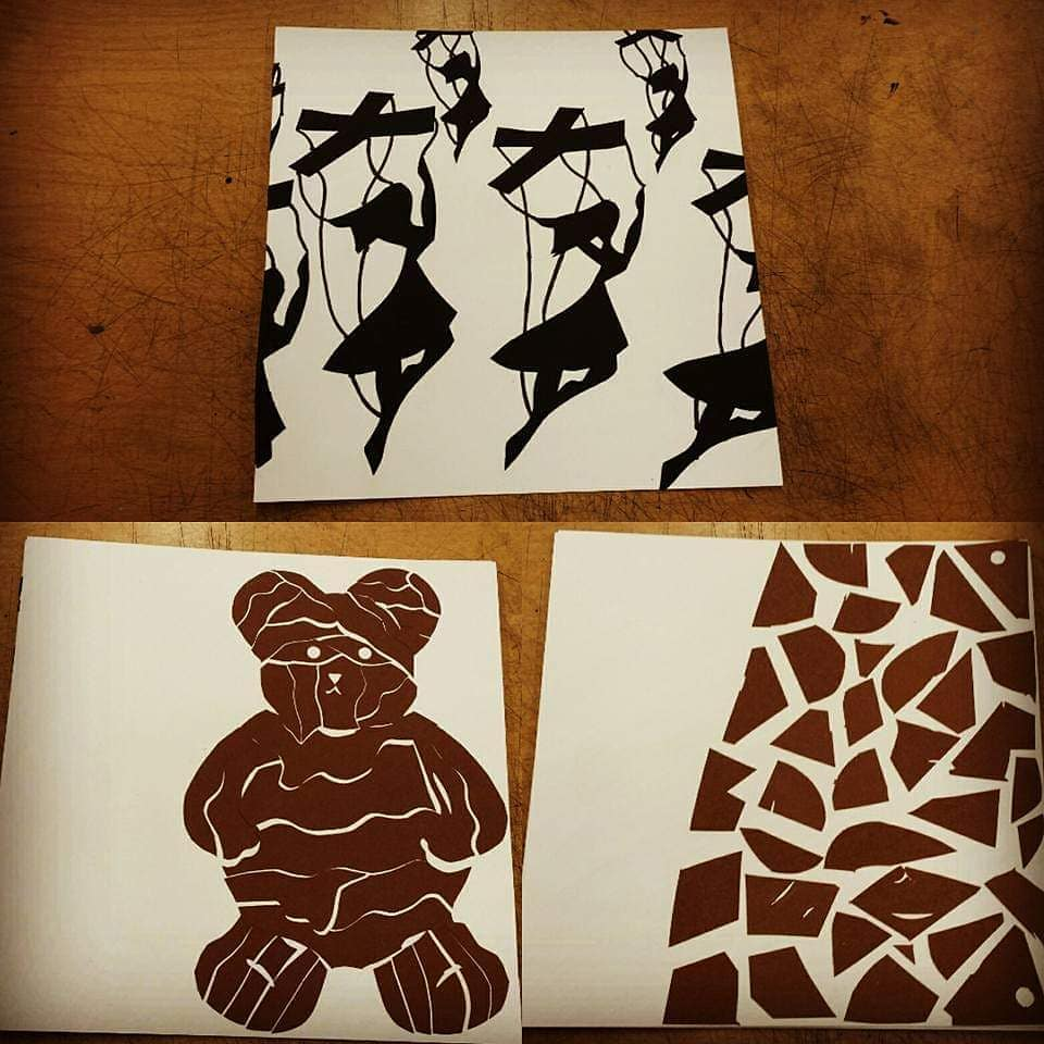 3 art pieces. 1 marionettes dance in a circle motion. 2nd is a bear cut into a puzzle. 3 is an abstract piece with brown puzzle pieces scattered to 2/3 of the right side of the page.